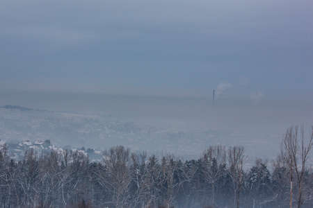 Polluted landscape, Chimneys growing over city covered by cloud of smog Krakow Poland Reklamní fotografie