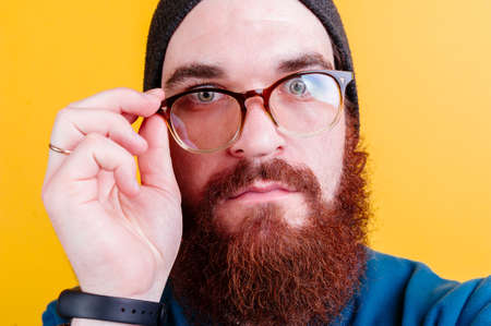 Serious bearded man touching eyeglasses over yellow background