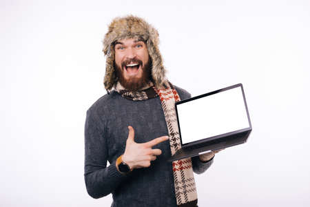 Excited bearded man wearing winter warm hat or cap, a scarf is poiting at his blank white screen laptop. Stock Photo