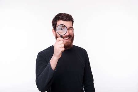 Handsome bearded man watching you through a magnifying glass on white background. Banco de Imagens