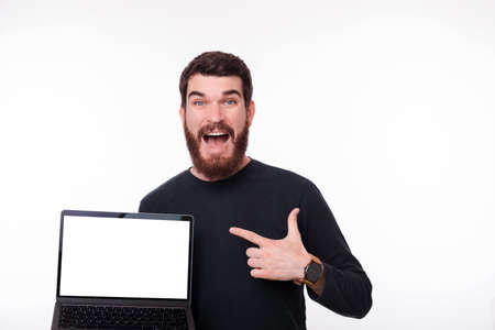 Surprised young bearded manis holding his laptop and pointing at it on white background. Blank white screen. Stock Photo