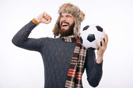 Bearded man making a winner gesture while holdiBearded man making a winner gesture while holding a soccer or football ball. Winter clothes.ng a soccer or football ball. Reklamní fotografie