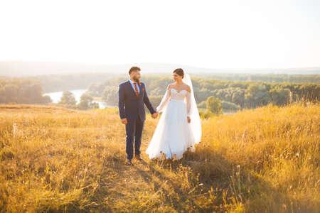 Eine Braut und ein Bräutigam gehen bei Sonnenuntergang auf einem Feld im Sonnenlicht und halten sich gegenseitig die Hände.