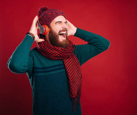 Happy bearded man is listening to the music on red background.