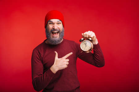 Cheerful bearded man standing over red background pointing at alarm clock