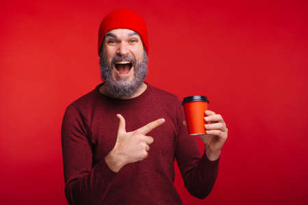 Amazed man with white beard pointing at red cup of coffee