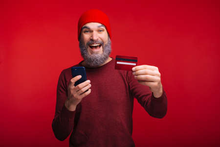 Portrait of happy man with beard using his credit card and smartphone, online web banking