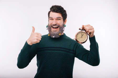 Cheerful handsome young man with white beard showing thumbs up and holding alarm clock