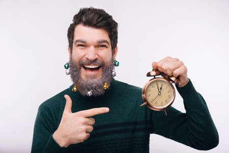 Close up photo of smiling man with decorated beard pointing at alarm clock, happy new year concept Reklamní fotografie