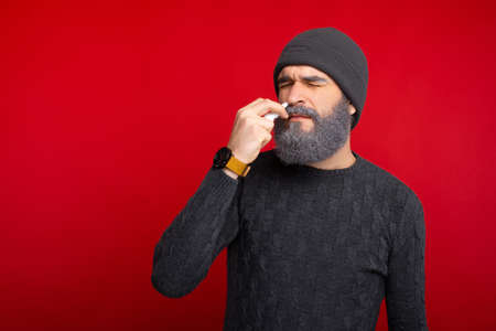Photo of bearded hispter man with a nasal spray , nose allergy Stock Photo