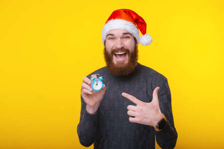 cheerful happy bearded hipster man pointing at small blue alarm clock Stock Photo