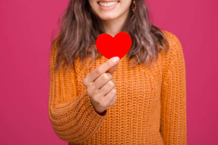 Happy woman holding red heart made from paper