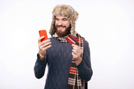 Happy man wearing winter clothes and using smartphone and credit card, online web banking