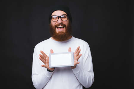 Photo of trendy bearded hipster man showing tablet blank screen Banque d'images - 135475343
