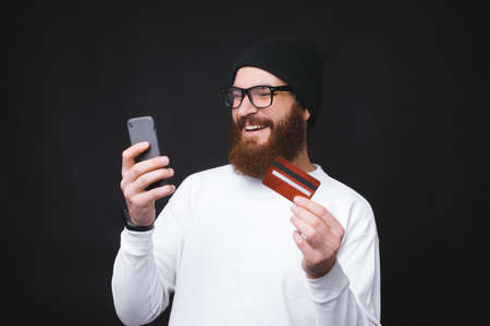 Young handsome man with beard making online shopping with phone and credit card Foto de archivo - 135500135