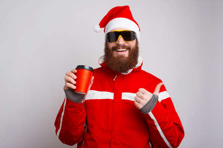 Photo of happy alpinist wearing santa claus hat holding cup of coffee to go and showing thumbs up