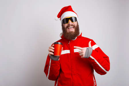 Photo of happy alpinist wearing santa claus hat pointing at cup of coffee