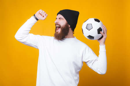Bearded joyful man is screaming and celebrating, holding a soccer ball on yellow wall.