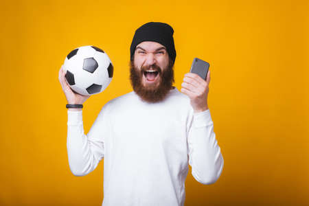 Young man is screaming and holding a phone and a soccer ball near yellow wall.