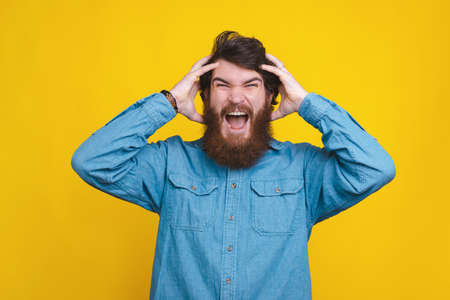 Photo of man in blue shirt screaming over yellow background