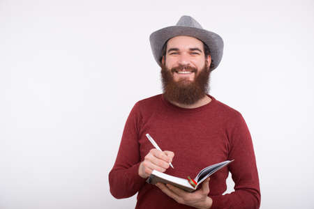 Happy bearded man wrinting in his new planner, time management