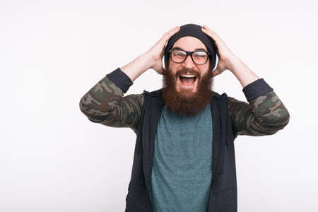 Photo of amazed bearded man screaming over white background Foto de archivo