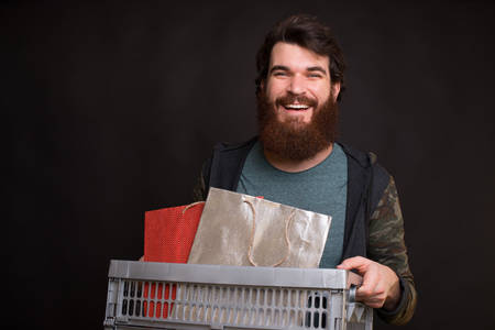 Photo of happy man holding box after shopping