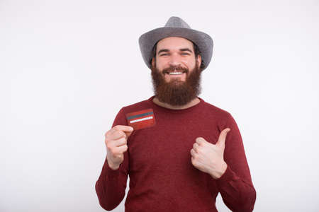 Portrait of smiling young bearded man showing credit card and thumbs up gesture