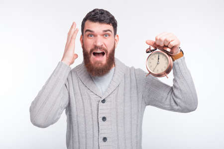 Bearded man holds an alarm clock and says Oh no, I am late, I forgot about the dead line.