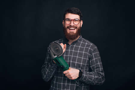 I am ready to repair. Young happy guy is holding a grinder.
