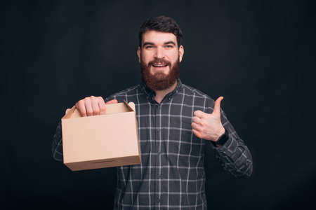 Young bearded man is holding a box for meals and shows like or thumb up gesture.