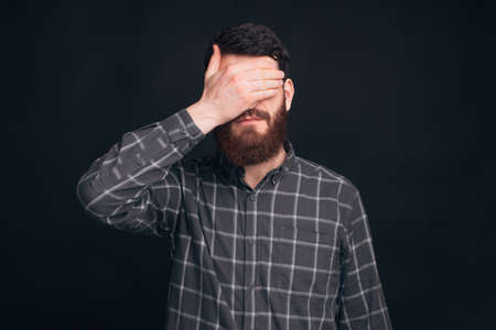 Handsome bearded man is covering his eyes and face with one hand on black background.