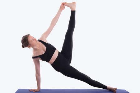 Woman practicing yoga on white background (side plank pose, vasisthasana) Stock Photo