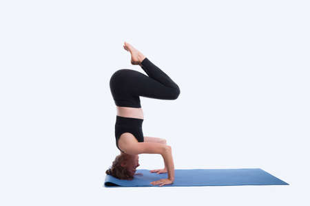 Beautiful young woman working out in a studio on white background, doing yoga exercise on blue mat, variation of supported headstand, garuda salamba sirsasana.