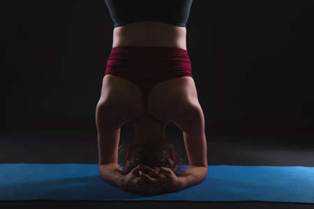 Beautiful young woman working out in a studio on black background, doing yoga exercise on blue mat, variation of supported headstand, garuda salamba sirsasana. Foto de archivo