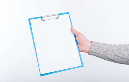 Blank paper on blue paper holder held by a man on white background.