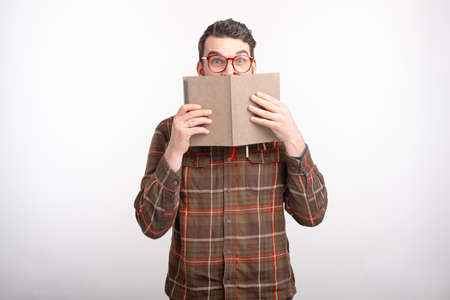 Amazed young man wearing glasses on white backgrounds is covering his face with an opened book. Reading time