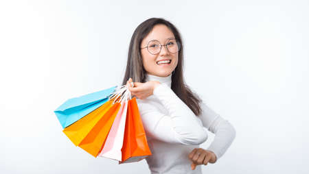 I like shopping. Happy girl is holding some colorful shopping bags on white background. Stok Fotoğraf