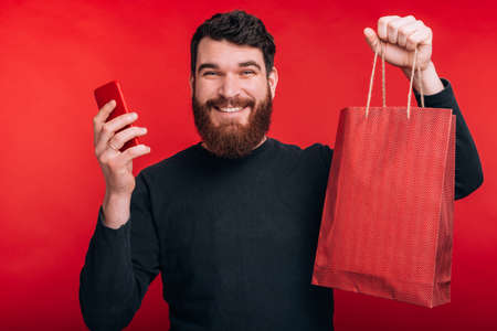 happy young man with beard holding smartphone and shopping bag, online shopping