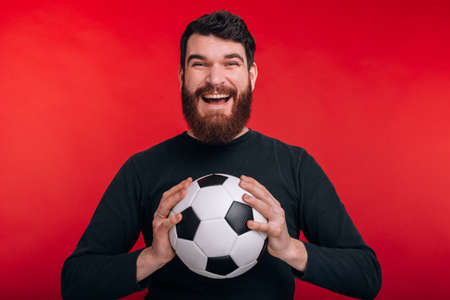 cheerful young man holding soccer ball and screaming over red backgroun