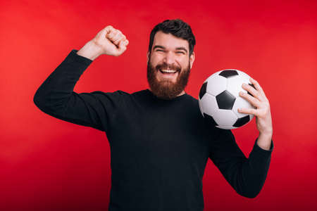 happy young man celebrating victory and holding soccer ball