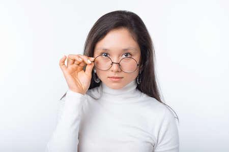 Retrato de una joven y bella mujer con gafas redondas y mirando confiado a la cámara