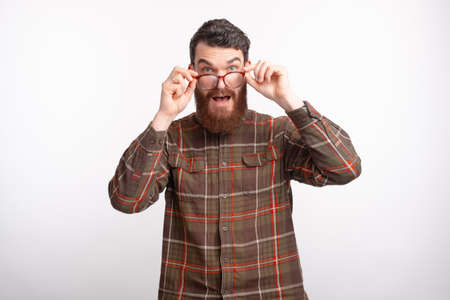 bearded man in checkered shirt looking at the camera and touching glasses
