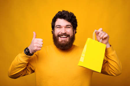 I appreciate the opportunity for online shopping. Smiling man is showing thumb up and yellow paper bag. Stok Fotoğraf