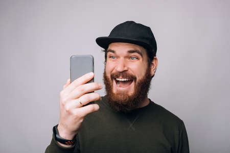 Surprised bearded man is looking at the phone, he has got some great news.