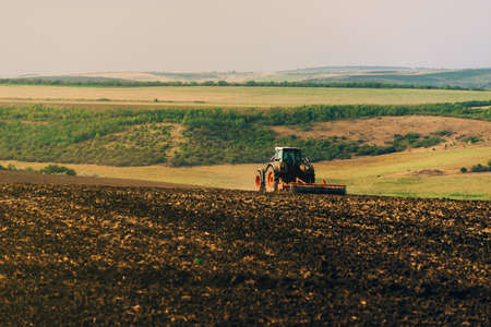 Photo of tractor cultivating a land, preparation for new year