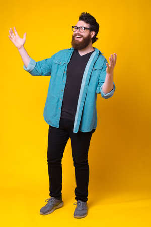 Full length photo of cheerful smiling young man making welcome gesture