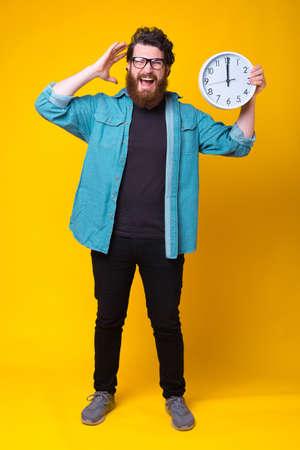 Full length photo of crazy bearded man holding big wall watch 免版税图像