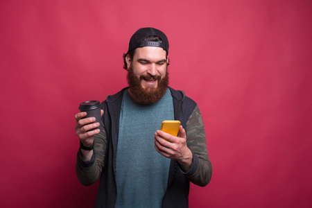 Smiling bearded man is looking at his phone while holding a paper cup over pink background