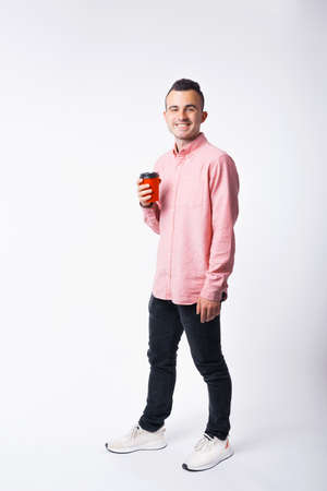 Full length portrait of young man smiling and drinking cup of coffee to go